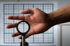 A multidirectional `perfect paraxial' cloak using four lenses. From a continuous range of viewing angles, the hand remains cloaked, and the grids seen through the device match the background on the wall (about 2 m away), in color, spacing, shifts, and magnification. /(Credit: J. Adam Fenster / University of Rochester)