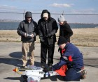Flying a radio-controlled replica of the historic WWII P-51 Mustang red-tail aircraft—of the legendary Tuskegee Airmen—NRL researchers (l to r) Dr. Jeffrey Baldwin, Dr. Dennis Hardy, Dr. Heather Willauer, and Dr. David Drab (crouched), successfully demonstrate a novel liquid hydrocarbon fuel to power the aircraft's unmodified two-stroke internal combustion engine. The test provides proof-of-concept for an NRL developed process to extract carbon dioxide (CO2) and produce hydrogen gas (H2) from seawater, subsequently catalytically converting the CO2 and H2 into fuel by a gas-to-liquids process (credit: U.S. Naval Research Laboratory).