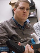 Ian Burkhart, who is paralyzed, playing a guitar video game, enabled by neural bypass system. (credit: The Ohio State Wexner Medical Center and Battelle)