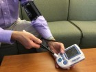 Dartmouth College Professor David Kotz demonstrates a commercial prototype of 'Wanda' imparting information such as the network name and password of a WiFi access point onto a blood pressure monitor. (credit: Dartmouth College)