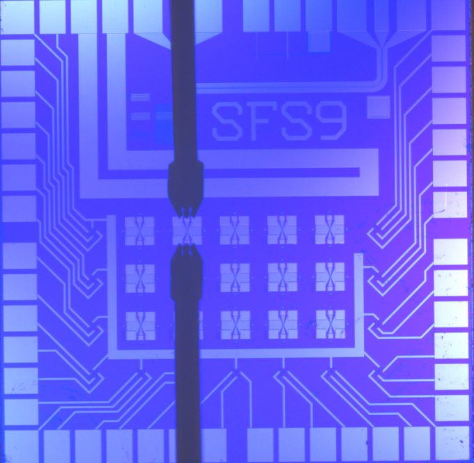 NIST's artificial synapse ,designed for neuromorphic computing, mimics the operation of a switch between two neurons. One artificial synapse is located at the center of each X. The thick black vertical lines are electrical probes for testing. This chip is 1 square centimeter in size. (credit: NIST)