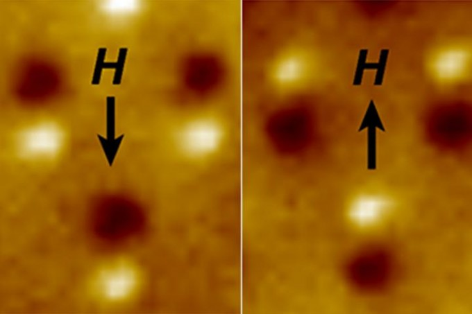 "Magnetic microscope image of three nanomagnetic computer bits. Each bit is a tiny bar magnet only 90 nanometers long. The microscope shows a bright spot at the ""North"" end and a dark spot at the ""South"" end of the magnet. The ""H"" arrow shows the direction of magnetic field applied to switch the direction of the magnets. (credit: Image by Jeongmin Hong and Jeffrey Bokor)"