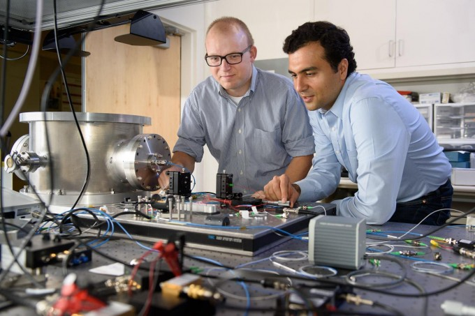 Post-doctoral scholar Peter McMahon, left, and visiting researcher Alireza Marandi examine a prototype of a new type of light-based computer. (credit: L.A. Cicero)