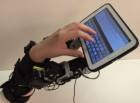 The 7-fingered hand can perform tasks that would usually require two hands, such as holding up a tablet computer and typing letters on it (credit: Harry Asad and Faye Wu)