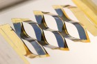 By borrowing from kirigami, the ancient Japanese art of paper cutting, researchers at the University of Michigan have developed solar cells that can track the sun. A flat plastic sheet backing the solar cells splits into wavy, connected ribbons when stretched. The tilt of the cells depends on the stretching, a simple mechanism for tracking the sun across the sky. (credit: Aaron Lamoureux)