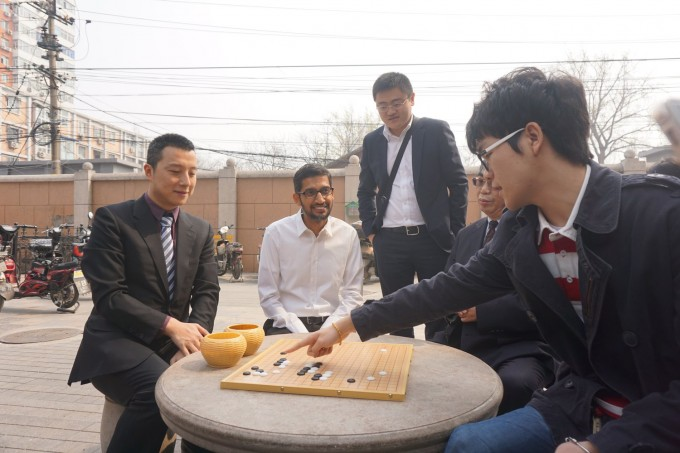 The world's number one Go player, Ke Jie (far right] and associates have recreated the opening moves of one of AlphaGo's games with Lee Sedol from memory to explain the beauty of its moves to Google CEO Sundar Pichai during a visit he made to Nie Weiping's Go school in Beijing last year (credit: DeepMind)