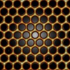 Precisely positioned carbon monoxide molecules (black) guide electrons (yellow-orange) into a nearly perfect honeycomb pattern called molecular graphene. Electrons in this structure have graphene-like properties; for example, unlike ordinary electrons, they have no mass and travel as if they are moving at the speed of light in a vacuum.  To make this structure, scientists from Stanford and SLAC National Accelerator Laboratory used a scanning tunneling microscope to move individual carbon monoxide molecules into a hexagonal pattern on a perfectly smooth copper surface. The carbon monoxide repels the free-flowing electrons on the copper surface, forcing them into a graphene-like honeycomb pattern (credit: Hari Manoharan/Stanford University)
