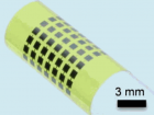 Ultra-thin solar cells flexible enough to bend around small objects, such as a 6-mm-diameter glass rod (credit: Juho Kim, et al./APL)