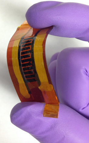 "Rice University scientists made this supercapacitor with interlocked ""fingers"" using a laser and writing the pattern into a boron-infused sheet of polyimide. The device may be suitable for flexible, wearable electronics. (Credit: Tour Group/Rice University)"