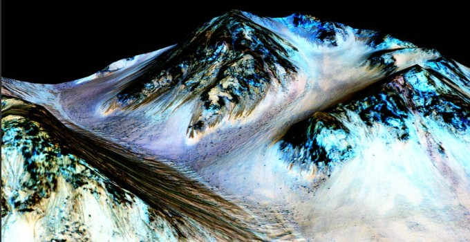 These dark, narrow, 100 meter-long streaks called recurring slope lineae flowing downhill on Mars are inferred to have been formed by contemporary flowing water. Recently, planetary scientists detected hydrated salts on these slopes at Hale crater, corroborating their original hypothesis that the streaks are indeed formed by liquid water. The blue color seen upslope of the dark streaks are thought not to be related to their formation, but instead are from the presence of the mineral pyroxene. (credits: NASA/JPL/University of Arizona)